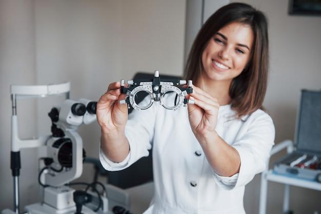 Otro equipo en la habitación. oftalmólogo femenino atractivo joven con dispositivo especial para probar los ojos de pie en la oficina.