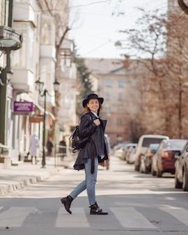 à â oung niña bonita camina por la ciudad sonriendo y posando