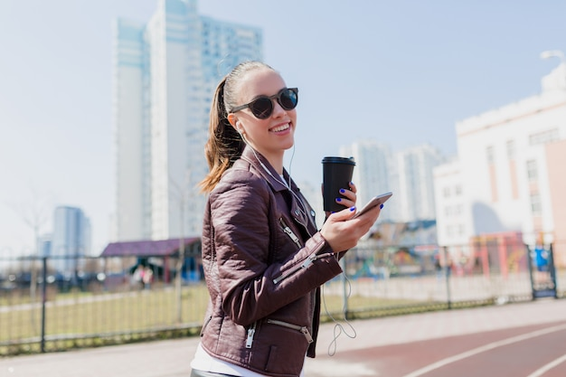 Outsdie retrato de encantadora mujer bonita sonriente con cabello oscuro vestida con chaqueta de cuero y gafas de sol negras escuchando música en auriculares