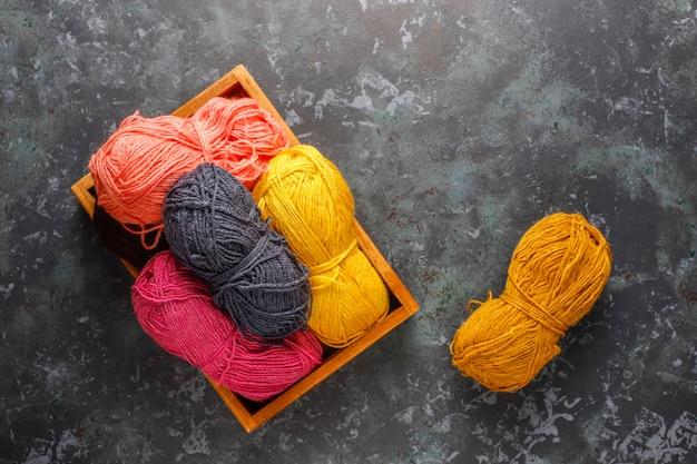 Ovillos de lana de diferentes colores con agujas de tejer.