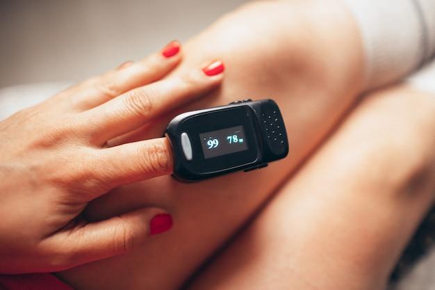 Oxímetro de pulso en la mano izquierda de la mujer. nivel de oxígeno y medición de pulso.