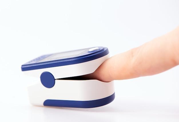Oxímetro de pulso utilizado para medir la frecuencia del pulso y los niveles de oxígeno a mano aislado sobre fondo blanco.