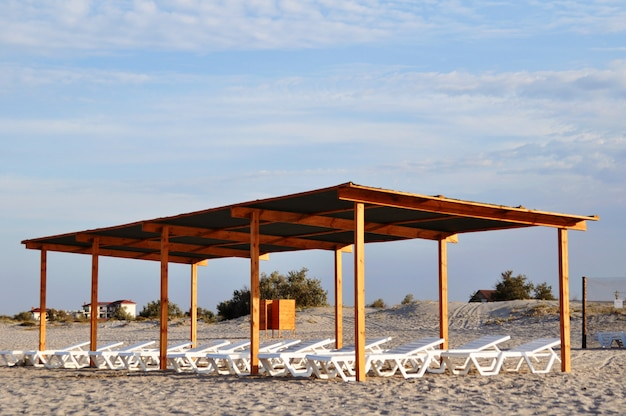 Pabellón de madera con tumbonas en la playa al amanecer.