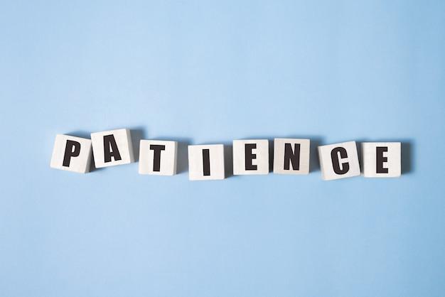 Paciencia palabra hecha con bloques de construcción sobre fondo azul.