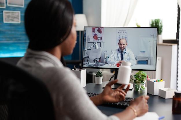 Paciente afroamericano discutiendo con el médico terapeuta durante la reunión de videollamada en línea