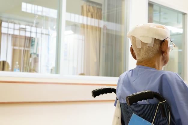 Paciente anciano con lesión en la cabeza en silla de ruedas en el hospital