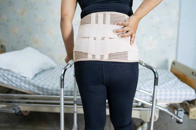 Paciente asiática con cinturón de soporte para el dolor de espalda para lumbar ortopédico con andador.