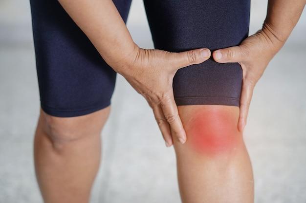 Una paciente asiática de mediana edad toca y siente dolor en la rodilla.