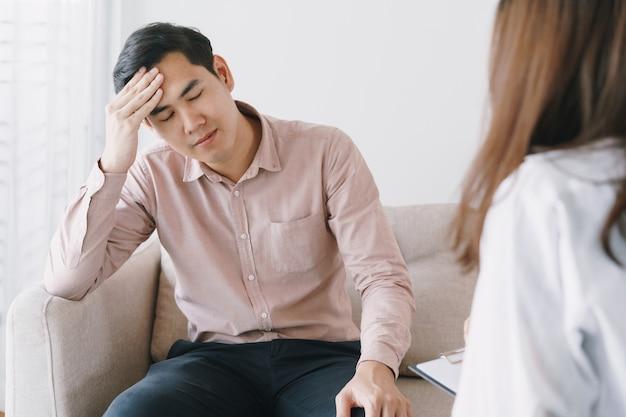 Paciente asiático masculino con psicólogo consultoría examen mujeres