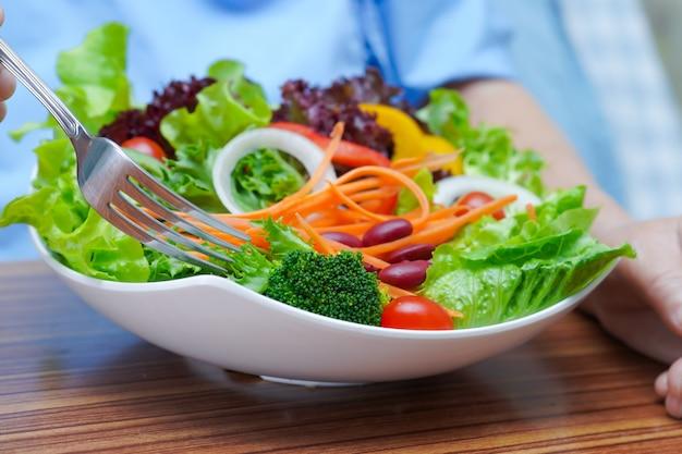 Paciente asiático mayor de la mujer que come la comida sana vegetal del desayuno.