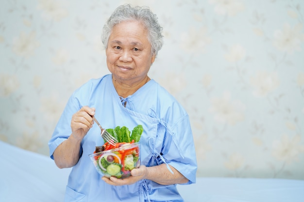 Paciente asiático mayor de la mujer que come la ensalada