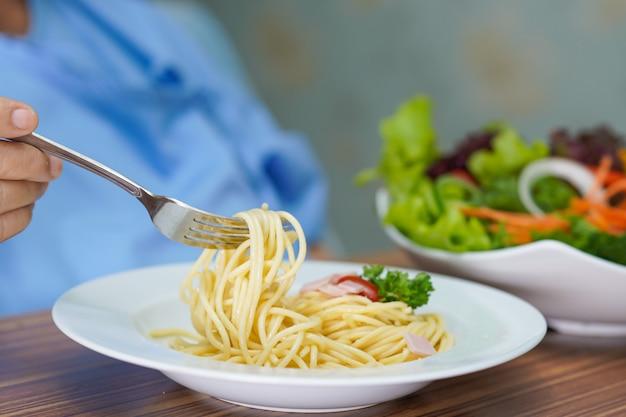 Paciente asiático mayor de la mujer que come el espagueti y la ensalada de carbonara.