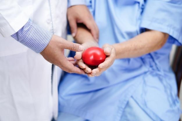 Paciente asiático mayor de la mujer que lleva a cabo el corazón rojo en su mano con el doctor.