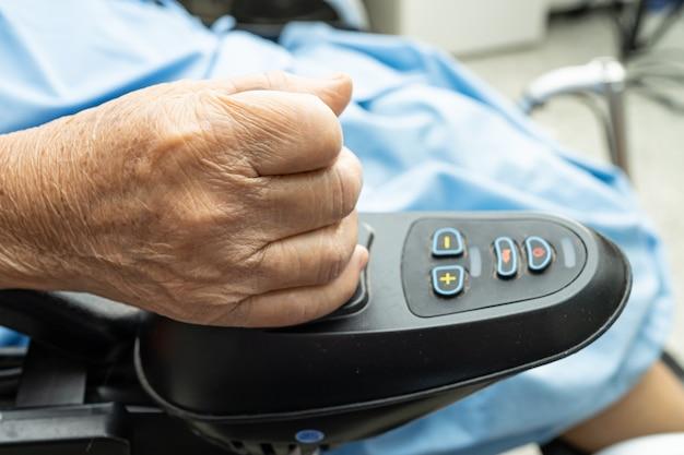 Paciente asiático mayor o anciano en silla de ruedas eléctrica con control remoto en la sala del hospital de enfermería, concepto médico fuerte y saludable
