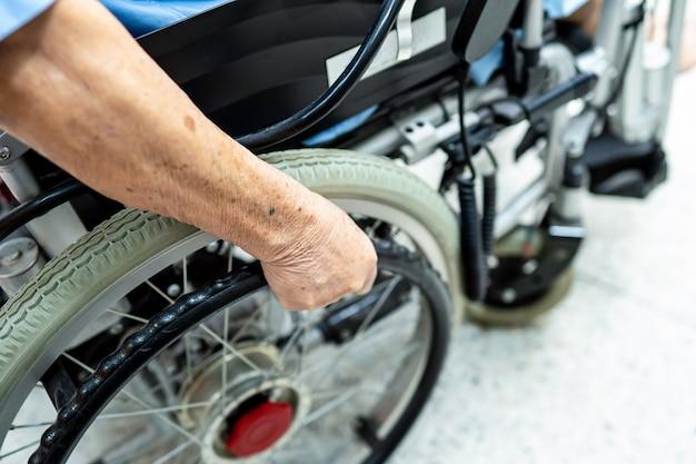 Paciente asiático mayor o anciano en silla de ruedas eléctrica con control remoto en la sala del hospital de enfermería