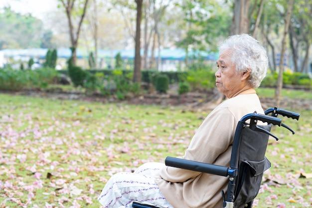 Paciente asiático mayor o mayor de la mujer de la señora mayor que sufre el dolor de la rodilla en la silla de ruedas en el parque, concepto médico fuerte sano.