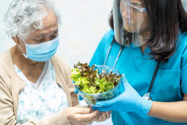 Paciente asiático de la mujer mayor que come el alimento vegetal del desayuno.