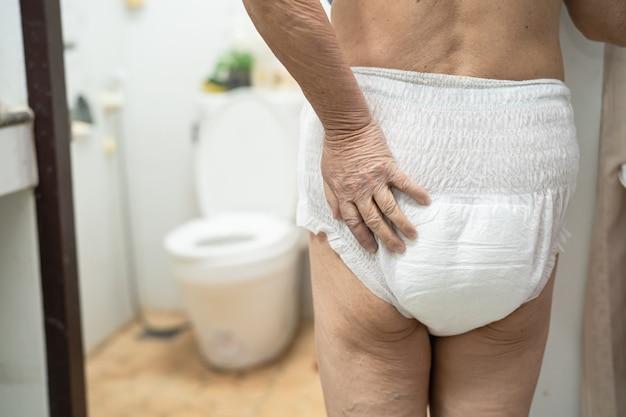 Paciente asiático de la mujer mayor que lleva el pañal de la incontinencia.