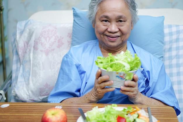 Paciente asiático de la mujer mayor que sostiene la comida sana.