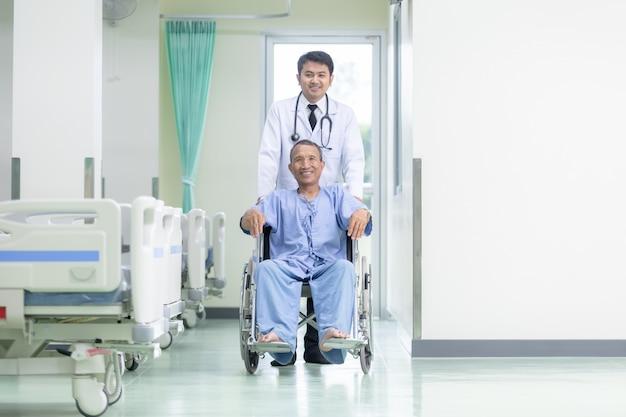 Paciente asiático en la silla de ruedas que se sienta en el pasillo del hospital con el doctor de sexo masculino asiático.