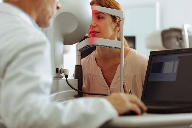 Paciente atractivo. atractiva mujer joven vistiendo elegante blusa con consulta de oftalmólogo