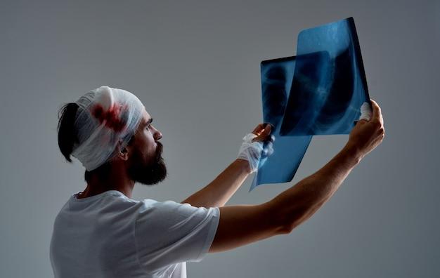 Paciente con la cabeza vendada examina radiografías en un medicamento de fondo gris. foto de alta calidad