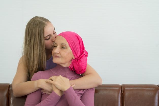 Paciente de cáncer de sexo femenino joven que pasa tiempo con su hija en casa.