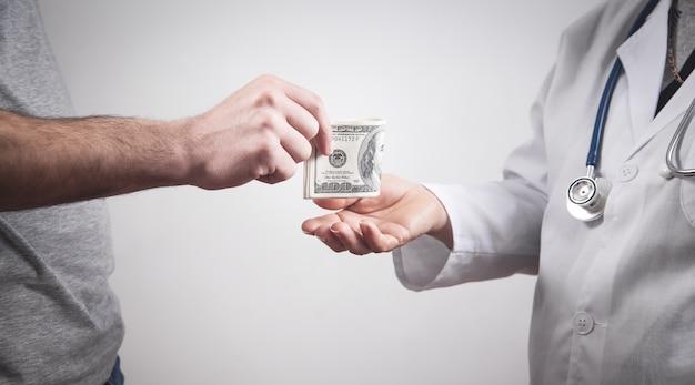 Paciente dando soborno al médico en la clínica.