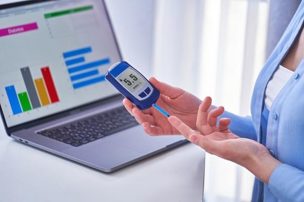 Paciente diabético que controla el nivel de glucosa en sangre con glucómetro