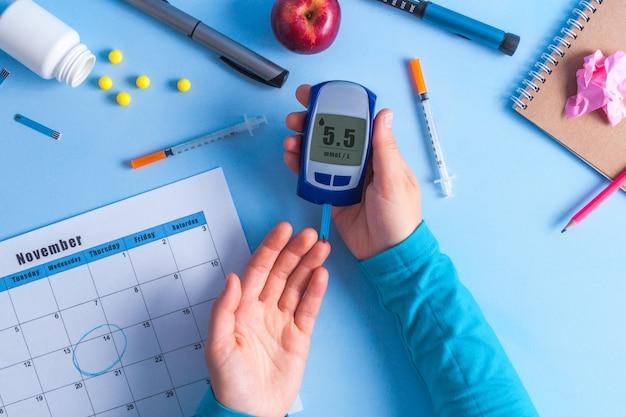 Paciente diabético usando medidor de glucosa para medir el nivel de glucosa.