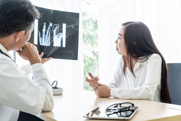 El paciente y el doctor femeninos asiáticos están discutiendo