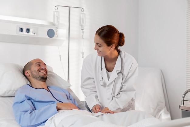 Paciente y doctor sonriente de tiro medio