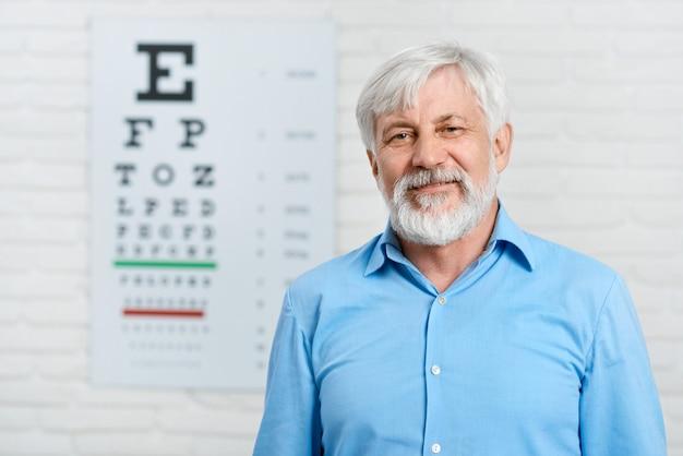 Paciente de edad que se encuentra frente a una mesa de inspección visual colgada en una pared blanca en un laboratorio oftalmológico.