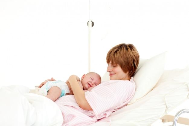 Paciente feliz con el bebé recién nacido en la cama