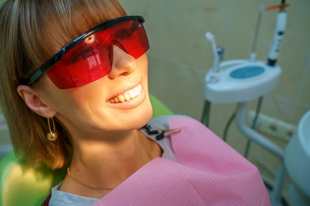 Paciente feliz de la odontología en la silla en gafas.
