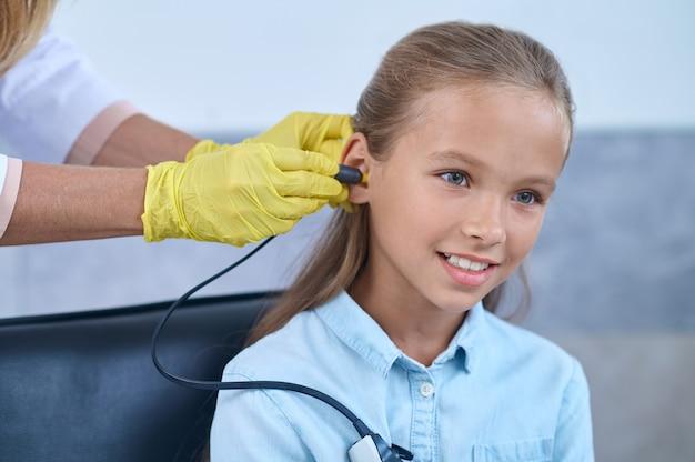 Paciente femenina complacida sometida a una prueba de audiometría