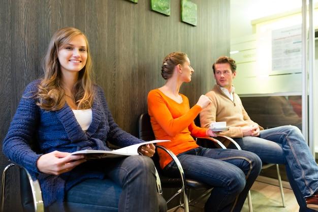 Paciente femenina en la recepción de la clínica, personas esperando su tratamiento