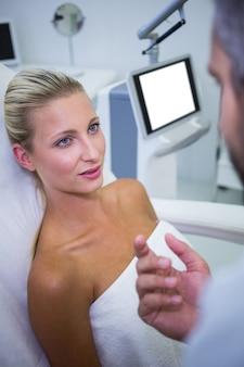 Paciente femenino acostado y mirando al médico