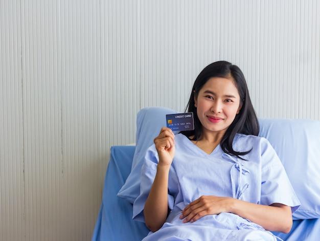 Paciente femenino asiático joven que sostiene la tarjeta de crédito y la sonrisa.