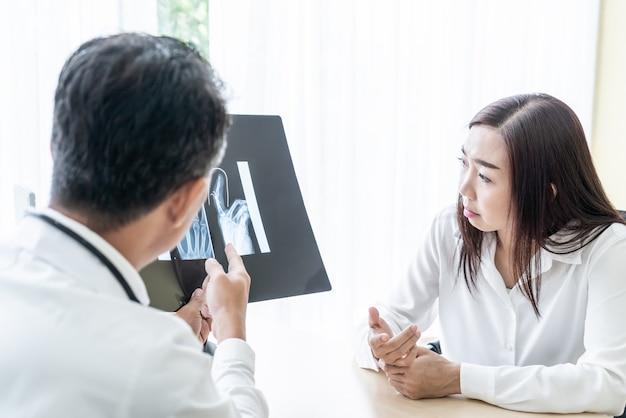 Paciente femenino asiático y médico están discutiendo