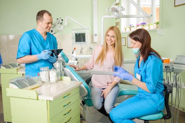 Paciente femenino con dos doctores en el consultorio dental.