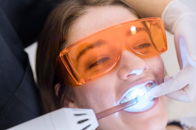 Paciente femenino con gafas protectoras de seguridad pasando por tratamiento de blanqueamiento dental con láser