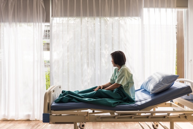Paciente femenino mayor solo que se sienta en cama en el hospital y que mira lejos fuera de la ventana que espera para ver a su familia para visitar.
