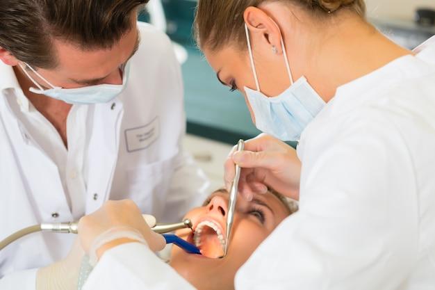 Paciente femenino con odontólogo y asistente dental, con máscaras y guantes.