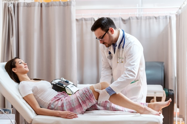 Paciente femenino en pijama acostada en la cama del hospital mientras el médico en uniforme blanco dobla su rodilla lesionada.