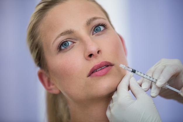 Paciente femenino que recibe una inyección de botox en la cara