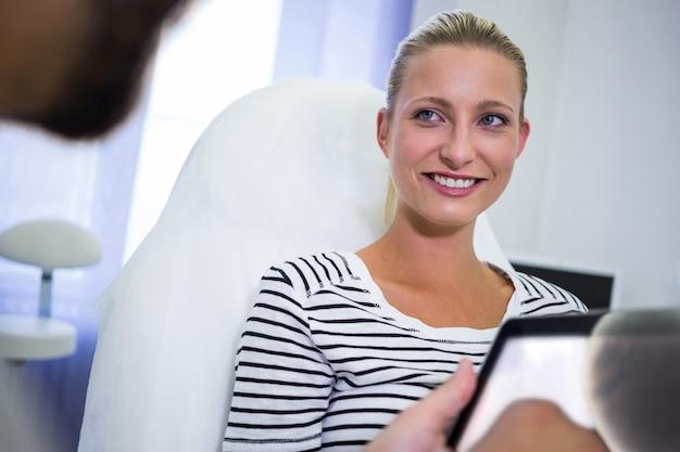 Paciente femenino sonriendo mientras mira al médico