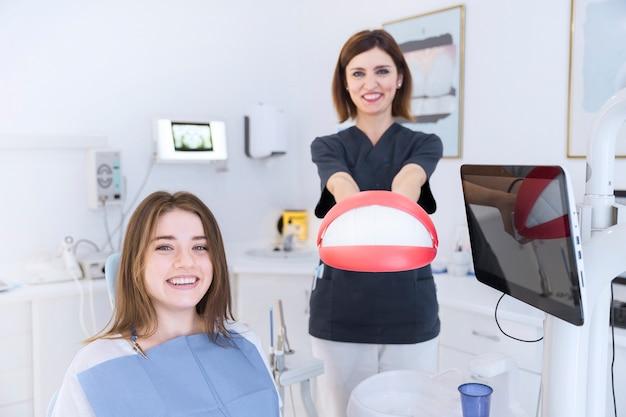 Paciente femenino sonriente delante del dentista que sostiene el modelo de los dientes en la clínica