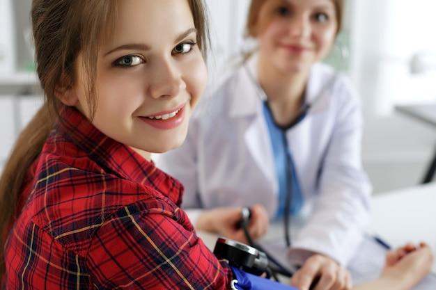 Paciente femenino sonriente sentado en el consultorio del médico de medicina