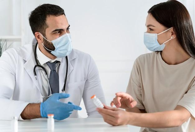 Paciente hablando con el médico con máscaras médicas.
